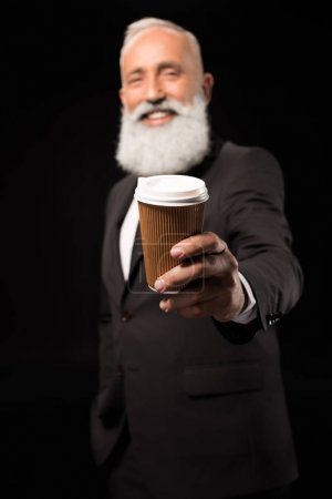 businessman holding out coffee
