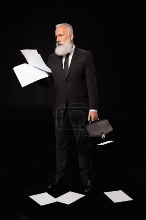 Photo pour Prise de vue complète d'un homme d'affaires en costume tenant des papiers et une mallette ouverte - image libre de droit
