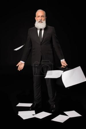 Photo pour Plan complet d'un homme d'affaires en costume entouré de feuilles de papier éparpillées - image libre de droit