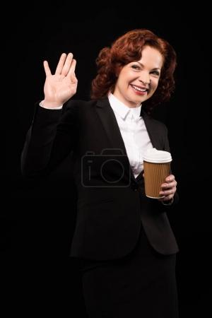Businesswoman holding coffee cup and waving