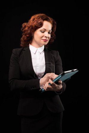 Businesswoman typing on digital tablet