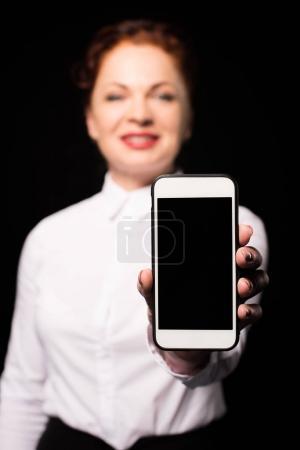 Photo pour Plan à mi-longueur d'une femme en chemise blanche tenant un smartphone et montrant l'écran à la caméra - image libre de droit