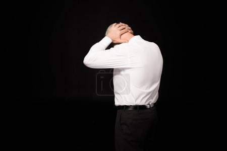 Photo for Rear view shot of  man in a suit clasping his hands on nape of neck - Royalty Free Image