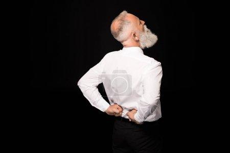 Photo pour Vue arrière de l'homme en costume se frottant le bas du dos - image libre de droit
