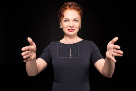 Photo for Half-length shot of woman in a black dress holding her hands forward, pretending to hold something - Royalty Free Image