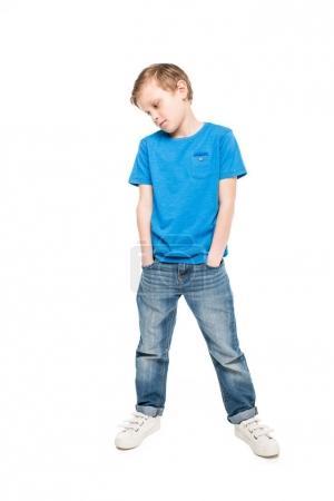 Photo pour Cher petit garçon debout avec les mains dans les poches et regardant vers le bas isolé sur blanc - image libre de droit