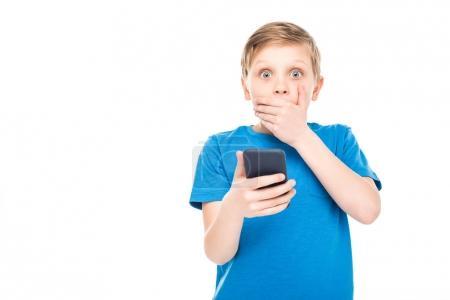 Photo pour Choqué petit garçon tenant smartphone et regardant caméra isolé sur blanc - image libre de droit