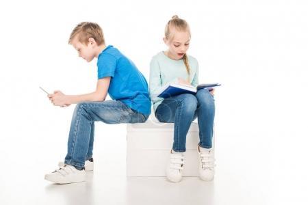Photo pour Enfants avec livre et tablette numérique assis ensemble isolé sur blanc - image libre de droit
