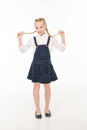 Photo for Adorable little girl holding her braids and smiling at camera isolated on white - Royalty Free Image