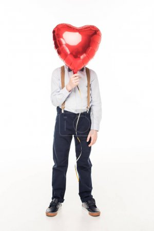 Photo for Stylish little boy hiding face behind red heart shaped balloon isolated on white - Royalty Free Image