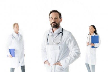 Photo pour Professionnel médecin masculin regardant caméra et collègues debout derrière, isolé sur blanc - image libre de droit