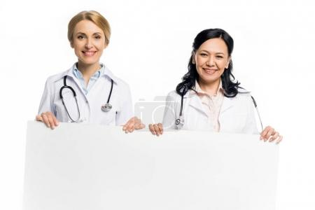 Photo for Professional multiethnic doctors holding blank banner and smiling at camera isolated on white - Royalty Free Image