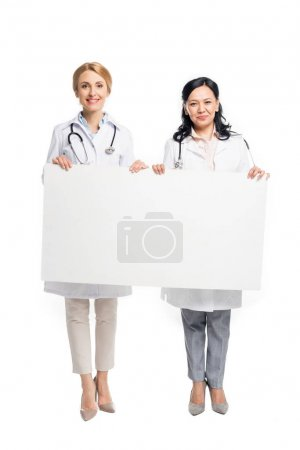Photo for Beautiful female doctors holding blank banner and smiling at camera isolated on white - Royalty Free Image