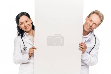 Photo for Cheerful multiethnic doctors holding blank banner and smiling at camera isolated on white - Royalty Free Image