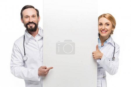 Photo for Cheerful doctors holding blank banner, showing thumb up and pointing with finger at copy space, isolated on white - Royalty Free Image