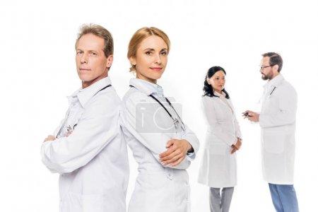 Photo pour Médecins confiants en blouses blanches debout avec les bras croisés et regardant la caméra isolée sur blanc - image libre de droit