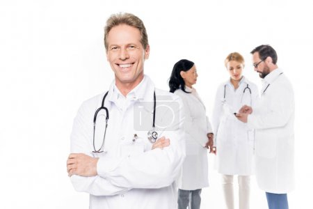 Photo for Handsome middle aged doctor standing with crossed arms and smiling at camera while colleagues standing behind, isolated on white - Royalty Free Image