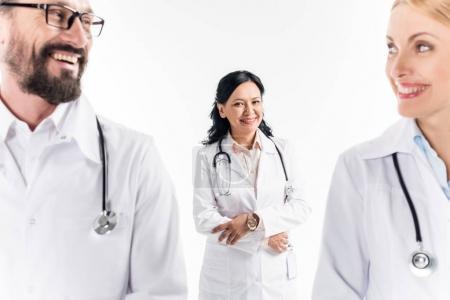 Photo pour Médecins professionnels d'âge moyen en manteaux blancs souriant isolé sur blanc - image libre de droit
