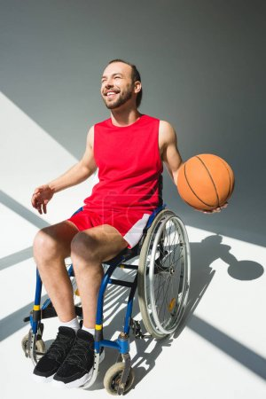 Sportsman in wheelchair holding basketball
