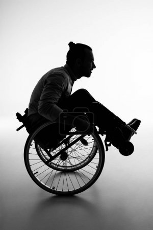 Photo for Side view shot of a young handicapped man in wheelchair - Royalty Free Image