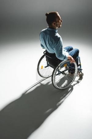 Photo for Physically handicapped man in wheelchair with shadow on white floor - Royalty Free Image