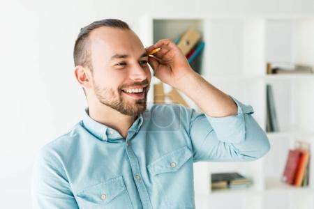 Photo pour Portrait d'un jeune homme souriant mettre crayon derrière l'oreille - image libre de droit
