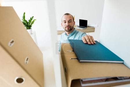 businessman reaching for notebook on shelf