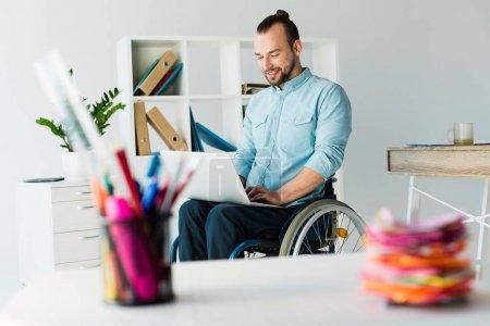 businessman in wheelchair using laptop