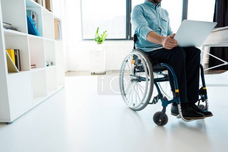 Photo for Cropped shot of businessman sitting in wheelchair using laptop in office - Royalty Free Image