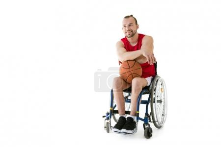 Photo for Smiling young sportsman sitting in wheelchair and holding basketball ball, isolated on white - Royalty Free Image