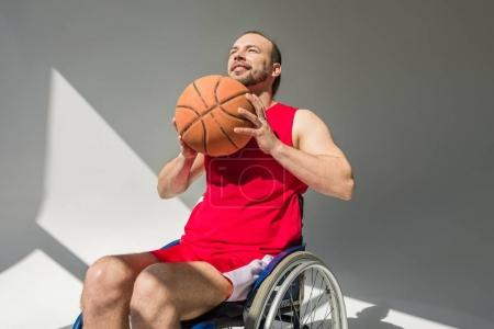 Disabled sportsman throwing basketball