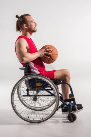 sportsman in wheelchair holding basketball
