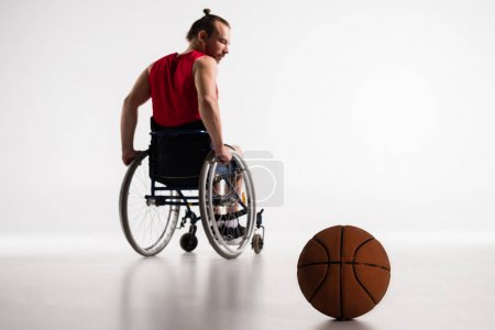 paralympic in wheelchair with basketball ball