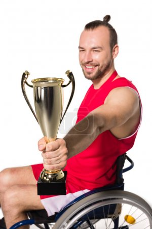 Sportsman in wheelchair with trophy