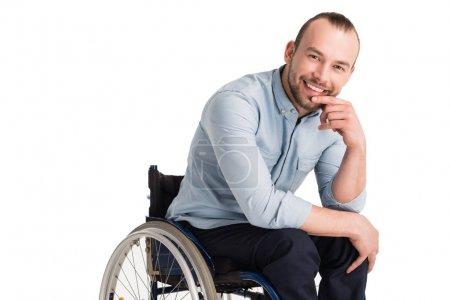 Photo pour Homme handicapé souriant en fauteuil roulant posant la main sur le menton et regardant la caméra, isolé sur blanc - image libre de droit