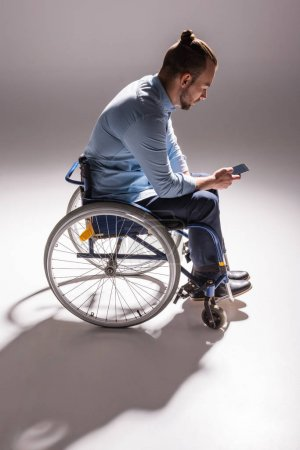 man in wheelchair using smartphone