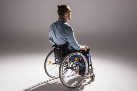 Photo for Physically handicapped man on wheelchair with shadow on white floor - Royalty Free Image
