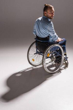 Photo pour Jeune homme souriant assis en fauteuil roulant et regardant la caméra - image libre de droit