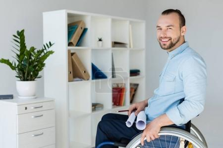 businessman in wheelchair holding documents