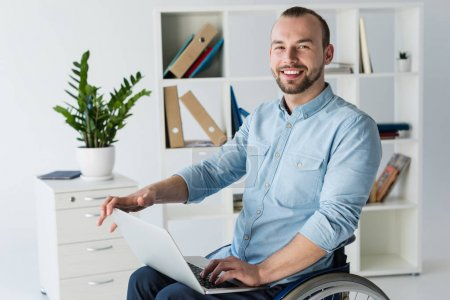 Photo for Smiling disabled businessman in wheelchair working with laptop in office - Royalty Free Image