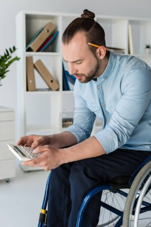 businessman in wheelchair using calculator