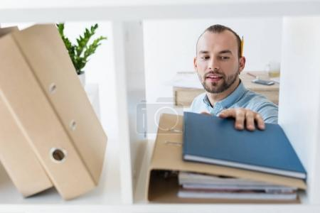 businessman reaching for paperwork on shelf