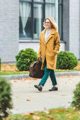 woman in yellow coat with leather bag