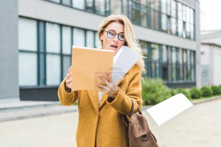 Businesswoman with paperwork on street