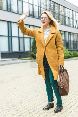 Photo for Attractive smiling woman in yellow coat with leather bag waving in park - Royalty Free Image