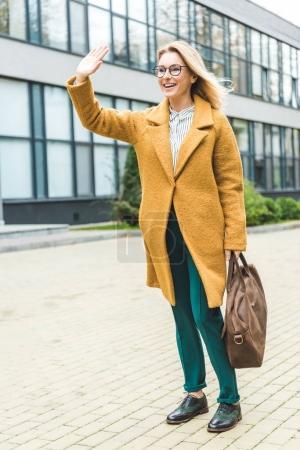 Photo pour Jolie femme souriante en manteau jaune avec sac en cuir ondulant dans le parc - image libre de droit