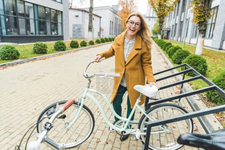 Photo for Cheerful attractive elegant woman with bicycle in city - Royalty Free Image