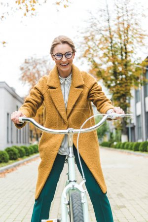 Photo for Attractive smiling woman in yellow coat riding bicycle in park - Royalty Free Image