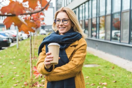 attractive woman with coffee in autumn park