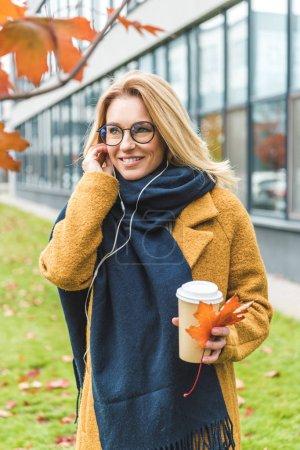 Photo pour Souriant belle femme avec café écouter de la musique dans le parc d'automne - image libre de droit